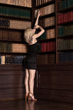 Erwachsene Blondine im sexy schwarzen Kleid, das nahen Weinlesebuh steht Lizenzfreie Stockfotos