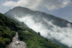 2 Erwachsene, die in den Bergen am nebelhaften Morgen wandern Lizenzfreie Stockbilder