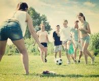 Erwachsene Familie mit vier Kindern, die Ball nachlaufen lizenzfreie stockfotos