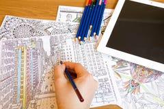 Erwachsene Farbtonbücher mit Bleistiften, neue Druckentlastungstendenz, Mindfulnesskonzeptperson färbend illustrativ lizenzfreies stockbild