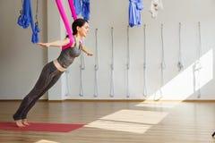 Erwachsene Frau übt aero Antigravitationsyogaposition im Studio Lizenzfreies Stockfoto