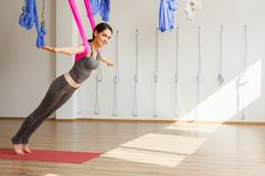 Erwachsene Frau übt aero Yogaposition im Studio Stockfoto
