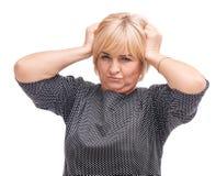 Erwachsene Frau, blond, lokalisiert auf dem weißen Hintergrund, halten durch das Haar Stockfotografie