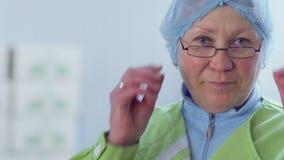 Erwachsene Frau in der Schutzkappe wendet sich an Kamera und entfernt Brillen vom Gesicht stock video