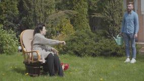 Erwachsene Frau des Porträts, die auf dem Rasen im Schaukelstuhl genießt Sonne sitzt Erwachsener Enkel kommt mit Wasser stock footage