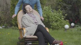 Erwachsene Frau des Porträts, die auf dem Rasen im Schaukelstuhl genießt Sonnennahaufnahme sitzt Erwachsener Enkel, der Augen von stock video footage
