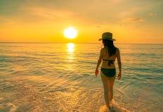 Erwachsene Frau des Schattenbildes, die in tropischem Meer mit schönem Sonnenunterganghimmel am Paradiesstrand geht Glücklicher M stockfoto