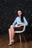 Erwachsene Frau, die auf einem Stuhl auf schwarzem Hintergrundziegelstein sitzt Stockfotografie