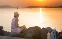 Erwachsene Frau, die den Sonnenuntergang nach einer langen Reise bewundert Stockbild
