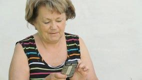 Erwachsene Frau, die draußen ein intelligentes Telefon hält stock video