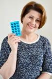 Erwachsene Frau, die eine Blisterpackung Pillen hält Lizenzfreie Stockbilder