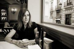 Erwachsene Frau, die einen Tasse Kaffee in einem Café nimmt stockbild
