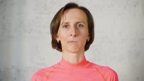 Erwachsene Frau, die heraus Backen während Gesichtseignungs-Frontkamera luftstößt Frauenschönheit Blogger, der Gesichtsgymnastik  stock footage