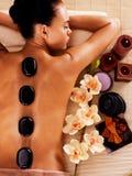Erwachsene Frau, die im Badekurortsalon mit heißen Steinen auf Körper sich entspannt Stockfoto