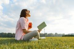 Erwachsene Frau, die im Park, sitzend auf dem Gras mit Buch- und Sommererfrischungsgetränk, goldene Stunde stillsteht lizenzfreie stockfotos