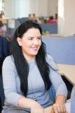 Erwachsene Frau, die Kunden über Kopfhörer mit Mikrofon beschäftigt Stockfotografie