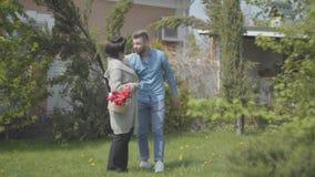 Erwachsene Frau, die mit dem Korb mit Tulpen in ihm auf dem Hinterhof geht Erwachsener Enkel kommt und umarmt die Dame, den Kerl stock video footage