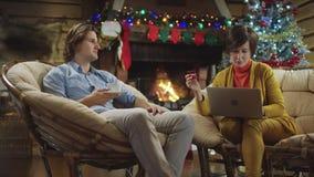 Erwachsene Frau, die online durch die Anwendung des Laptops und der Kreditkarte auf Heiliger Nacht kauft, während ihr Sohn Kaffee stock video footage