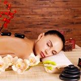 Erwachsene Frau, die sich an im Badekurortsalon mit heißen Steinen zurück entspannt Stockbild