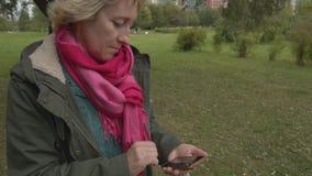 Erwachsene Frau, die Smartphone im Park verwendet stock video