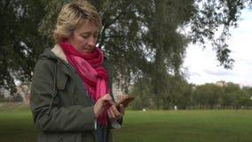 Erwachsene Frau, die Smartphone im Park verwendet stock video footage