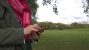 Erwachsene Frau, die Smartphone im Park verwendet stock footage