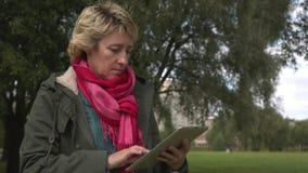Erwachsene Frau, die Tabletten-PC im Park verwendet stock video