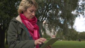 Erwachsene Frau, die Tabletten-PC im Park verwendet stock video footage