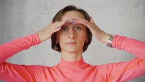 Erwachsene Frau, die vordere Kamera der Gesichtsmassage tut Nahe hohe Frau, die Hautgesichtsmassage tut Mimische Gymnastik für Ve stock video