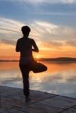 Erwachsene Frau, die Yogaübungen bei Sonnenuntergang tut Stockfotografie