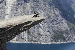 Erwachsene Frau, die zur?ck auf Trolltunga-Klippe auf seinem liegt Machen von selfie Foto mit Smartphone norwegen stockfotografie
