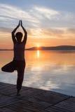 Erwachsene Frau entspannen sich, beim Handeln von Yoga trainiert auf Plattensee Lizenzfreie Stockbilder