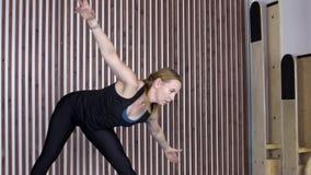 Erwachsene Frau führt eine Übung durch, um Muskeln von Armen, von Beinen und von Dorn zu entwickeln stock footage