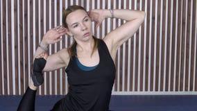 Erwachsene Frau führt komplexe gymnastische Übung beim Üben von Yoga durch stock footage