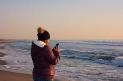 Erwachsene Frau geht durch das Meer, auf der Küstenlinie und überprüft ihren Handy stockbild