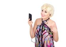 Erwachsene Frau im pareu hört Musik mit Mobiltelefon Lizenzfreies Stockfoto