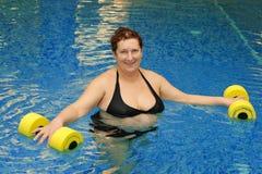 Erwachsene Frau im Wasser mit Dumbbells Stockbilder