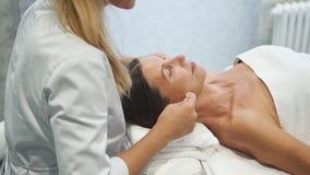 Erwachsene Frau liegt auf Massagetabelle und erhält Gesichtsgesundheitswesen-Behandlungstherapie stock footage