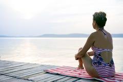 Erwachsene Frau meditiert auf dem Ufer des silbernen Wassers Lizenzfreie Stockbilder