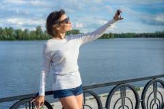 Erwachsene Frau tut selfie unter Verwendung eines Smartphone Blauer Himmel des Hintergrundes mit Wolken, Fluss Stockfoto