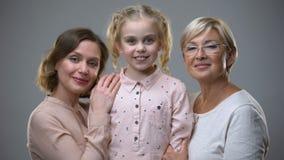 Erwachsene Frauen, die wenig Mädchen auf grauem Hintergrund, Liebe für Kind, Familiensorgfalt umarmen stock video