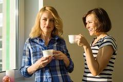 Erwachsene Frauen trinken Kaffee, sprechen, lachen Lizenzfreie Stockfotos