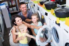 Erwachsene glückliche Familie, die Waschmaschine wählt lizenzfreie stockbilder