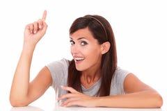 Erwachsene glückliche Frau, die herauf ihren Finger zeigt Lizenzfreie Stockfotos
