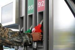 Erwachsene Hand, die Zapfpistole an der Tankstelle hält Stockbild