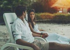 Erwachsene Jungvermählten, die auf Liege auf einem Strand sitzen Stockbilder