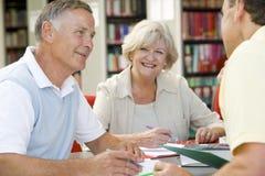 Erwachsene Kursteilnehmer, die in einer Bibliothek zusammenarbeiten Lizenzfreies Stockfoto