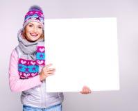 Erwachsene lächelnde Frau im Winterhut hält die weiße Fahne Lizenzfreie Stockfotos
