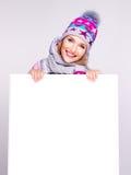 Erwachsene lächelnde Frau im Winterhut hält die weiße Fahne Stockfotos