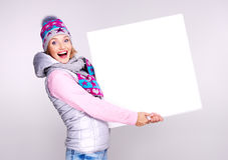 Erwachsene lächelnde Frau im Winterhut hält die weiße Fahne Lizenzfreie Stockfotografie